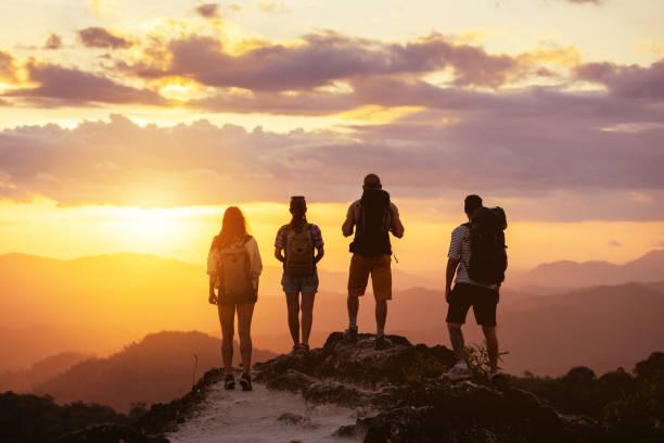 산 꼭대기의 4인 실루엣이 일몰을 바라본다 - mountain top 뉴스 사진 이미지
