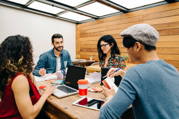 Four persons multiethnic startup discussing ideas in the office stock photo