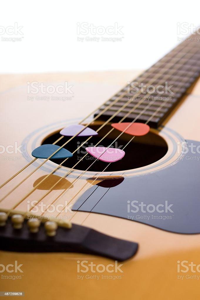 Four picks in guitar strings stock photo