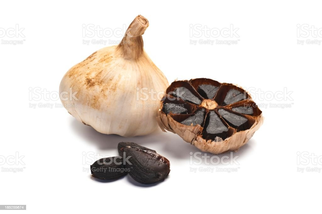 Four Pieces of black garlic in various stages of preparation stock photo