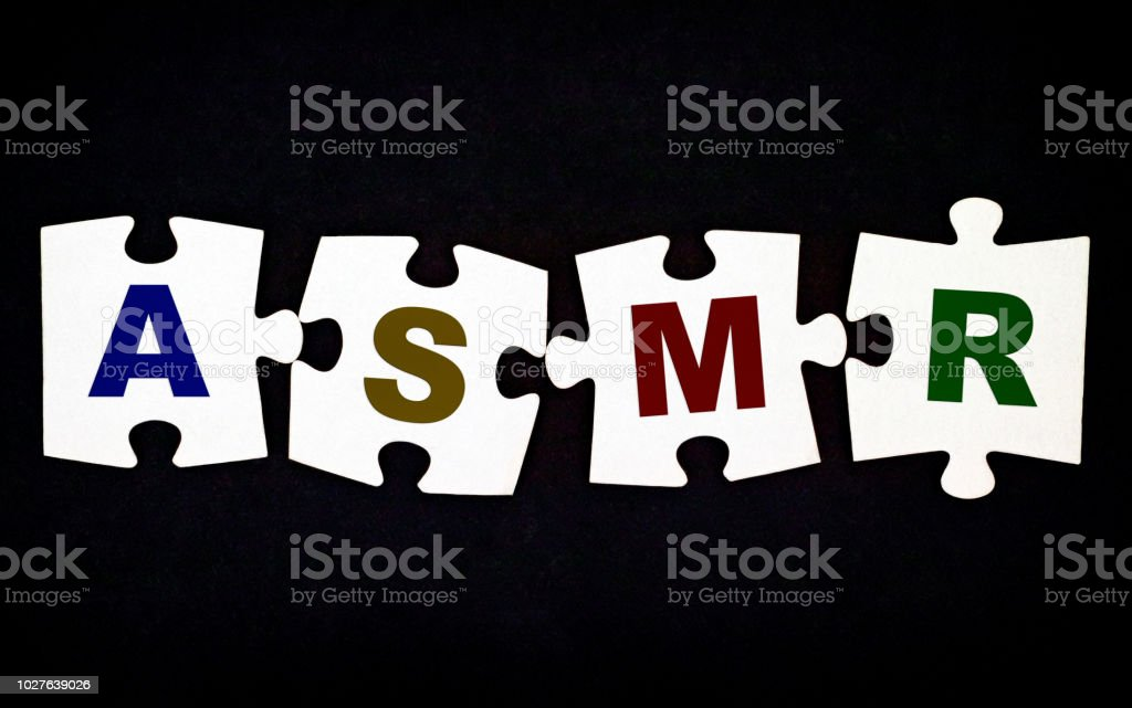 Four pieces of puzzle with letters ASMR on black background. – zdjęcie