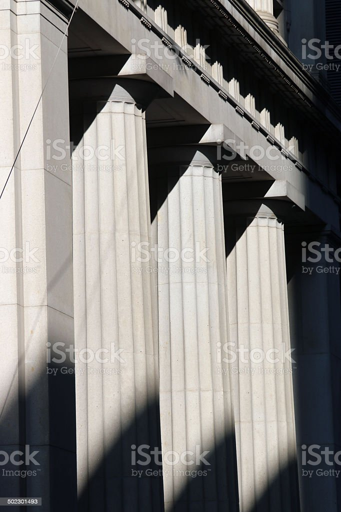 Four pillars in a row with dark shadows at bottom stock photo