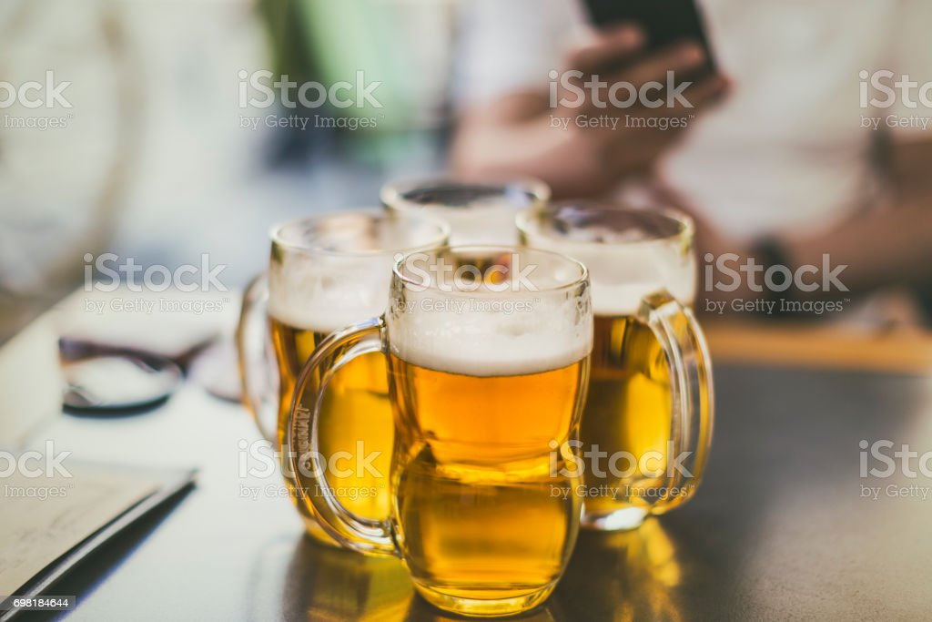 Four pilsner beer mugs on a table, as shot in Prague. stock photo
