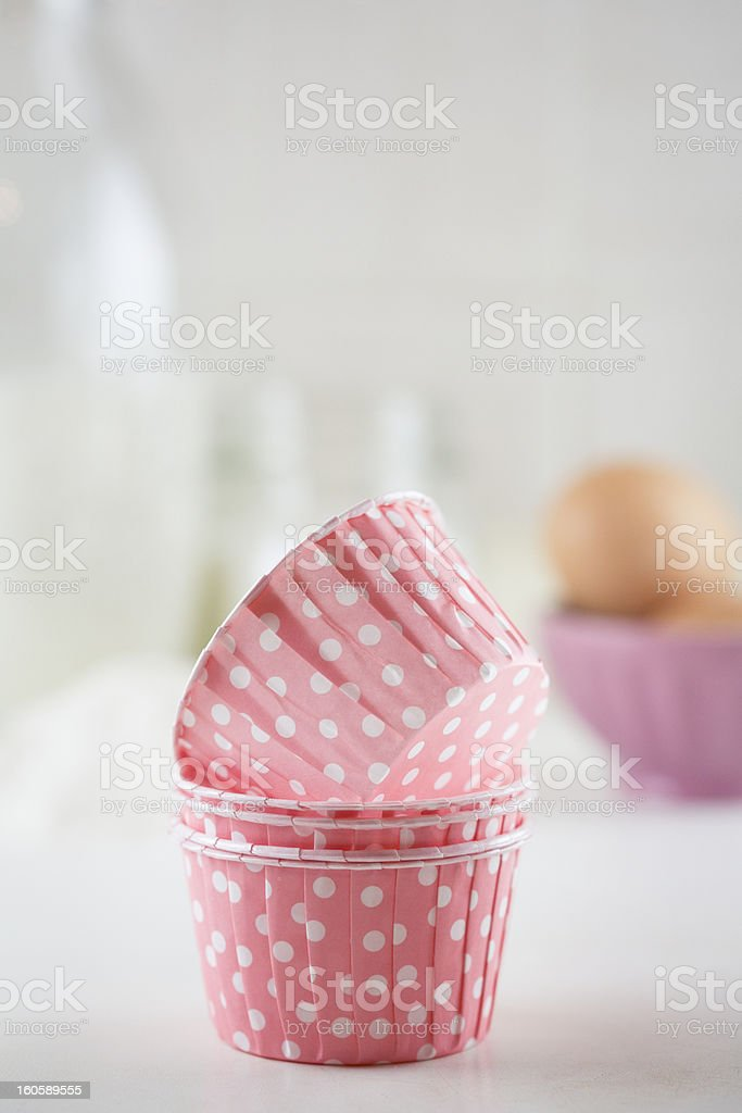 Four pink cupcake liners and ingredients for the recipe stock photo