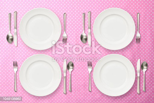 Overhead shot of four place setting on pink polka dot tablecloth.