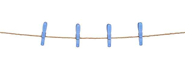 Four plastic clothespins on rope stock photo