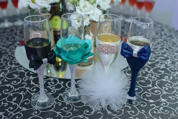 vier spielerisch verzierte querflöte gläser für eine hochzeit mit fliege und pompons, die ähnlich wie die braut und bräutigam outfits - hochzeitskleid in schwarz stock-fotos und bilder