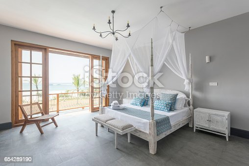 Simple bedroom with large open window and rustic furniture, Sri Lanka