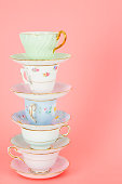 istock Four Pretty Old Fashioned Antique Teacups Stacked On Pink 163907186