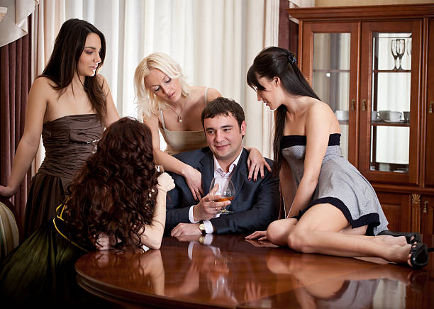 Four pretty women seduce à one man in a room stock photo