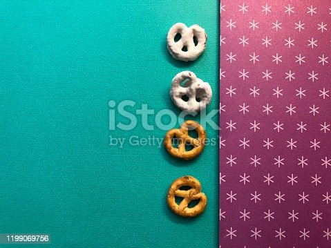 2 plain and 2 white chocolate covered pretzels on a green and purple and white starred background.