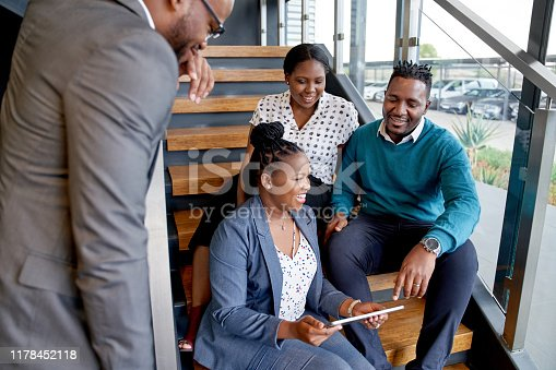 istock Four professional male and female coworkers sitting on staircase smiling practicing teamwork on corporate tablet 1178452118