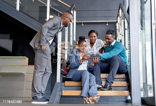istock Four professional male and female coworkers sitting on staircase smiling practicing teamwork on corporate tablet 1178452483
