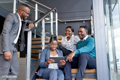 istock Four professional male and female coworkers sitting on staircase smiling practicing teamwork on corporate tablet 1178452489
