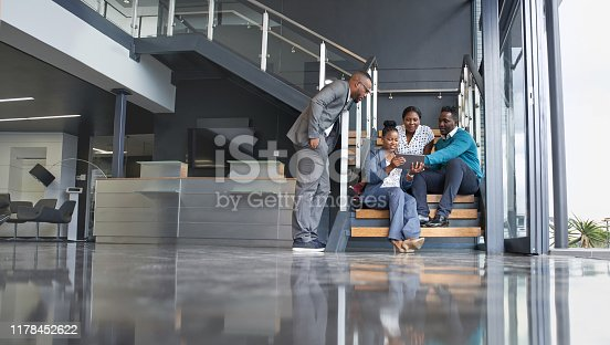 istock Four professional male and female coworkers sitting on staircase smiling practicing teamwork on corporate tablet 1178452622