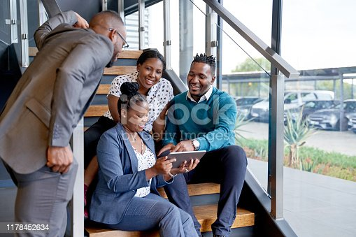 istock Four professional male and female coworkers sitting on staircase smiling practicing teamwork on corporate tablet 1178452634
