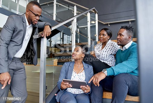istock Four professional male and female coworkers sitting on staircase smiling practicing teamwork on corporate tablet 1179885401