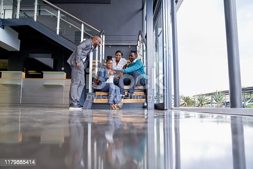 istock Four professional male and female coworkers sitting on staircase smiling practicing teamwork on corporate tablet 1179885414