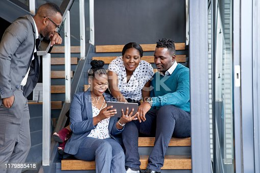 istock Four professional male and female coworkers sitting on staircase smiling practicing teamwork on corporate tablet 1179885418