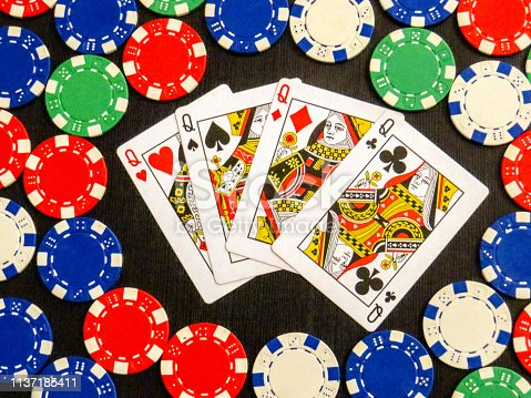 Four Q in poker cards with poker chips