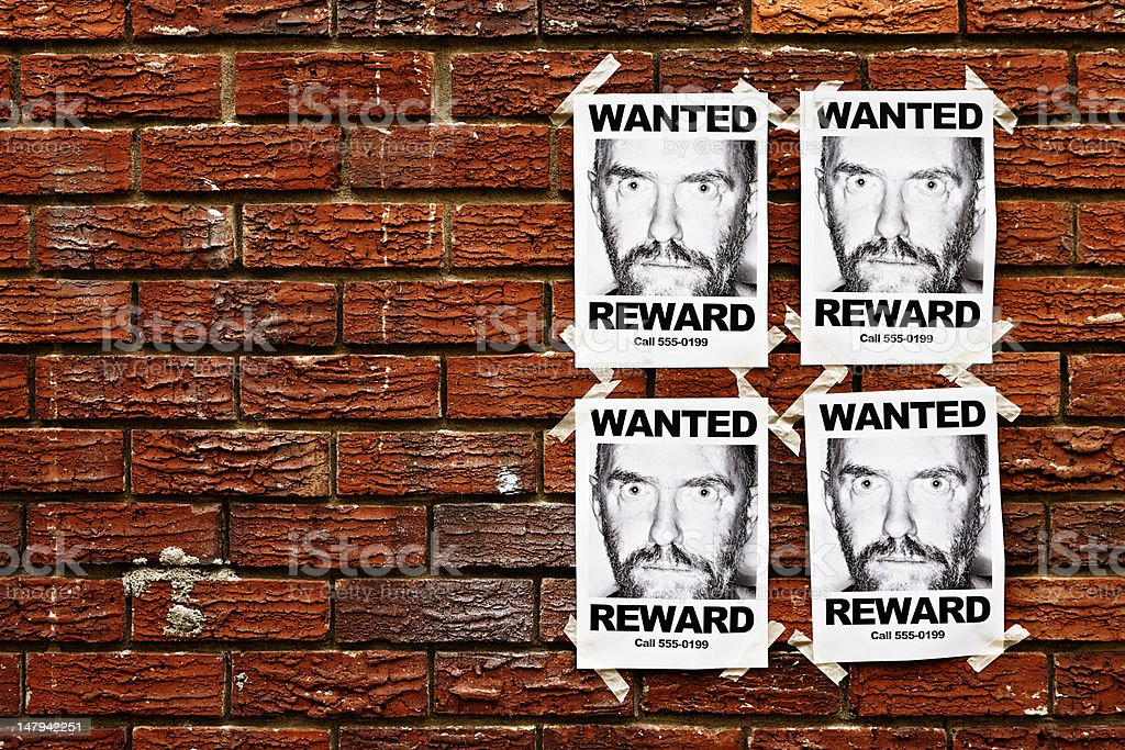 """Four """"Wanted"""" posters of scary looking man taped to wall royalty-free stock photo"""