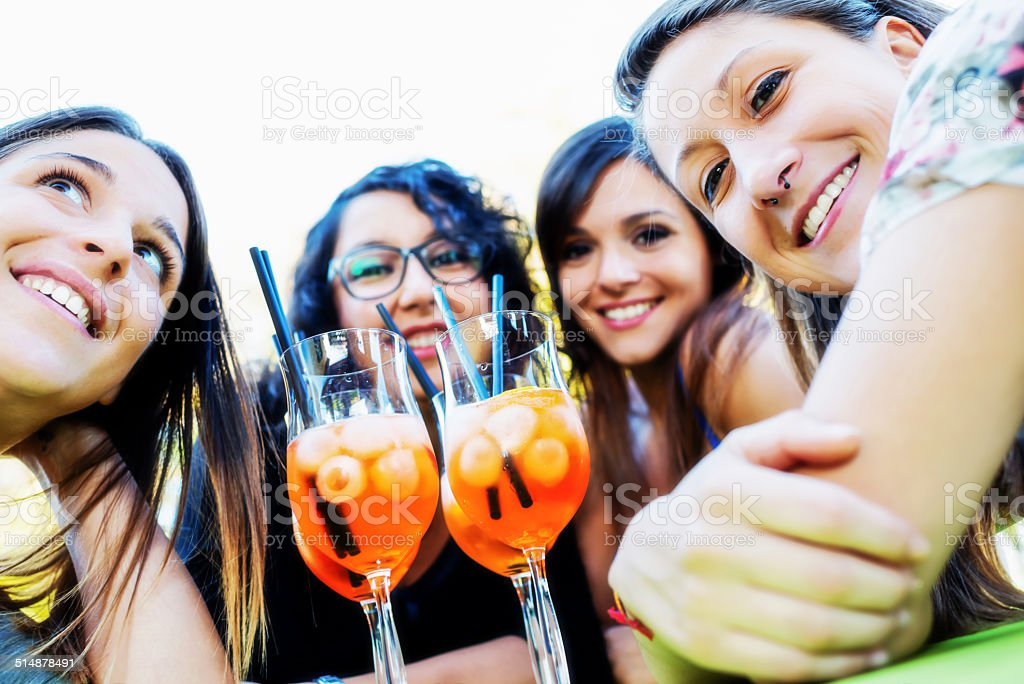 Four real girfriends with glasses of cocktail stock photo