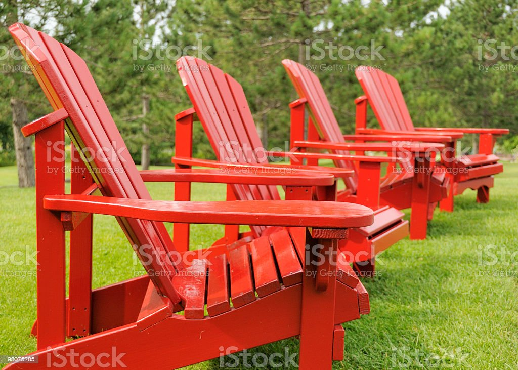 Four red Adirondack chairs royalty-free stock photo