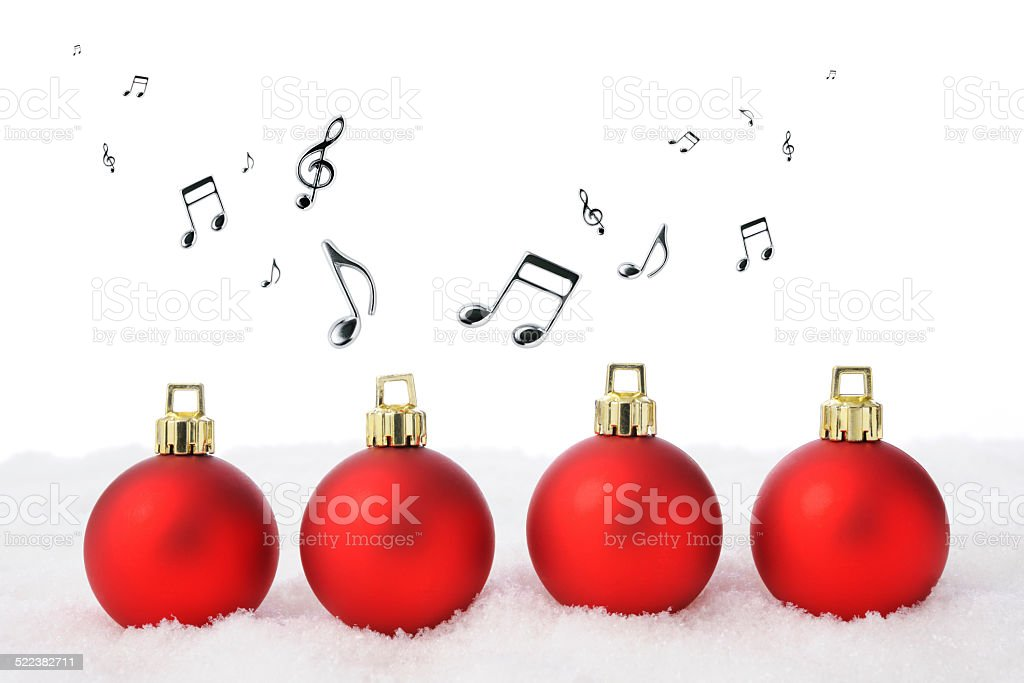 Four red Christmas balls on the snow with musical note stock photo