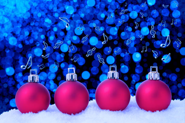 Four red Christmas ornaments on the snow, and flying musical note stock photo