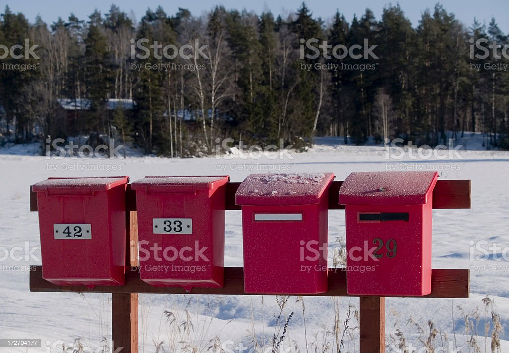 Four red frost covered mailboxes stock photo