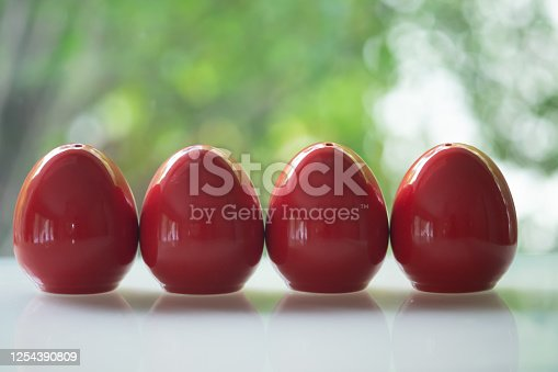 Four red of egg shape ceramic shakers for salt and pepper on table