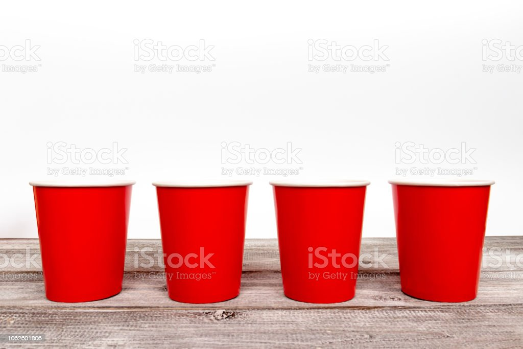 Four red paper disposable cups for coffee and nonalcoholic drinks on...
