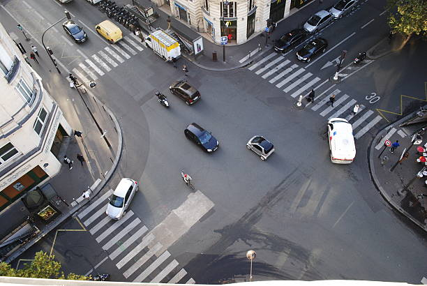 four road junction with cars in paris - kruispunt stockfoto's en -beelden