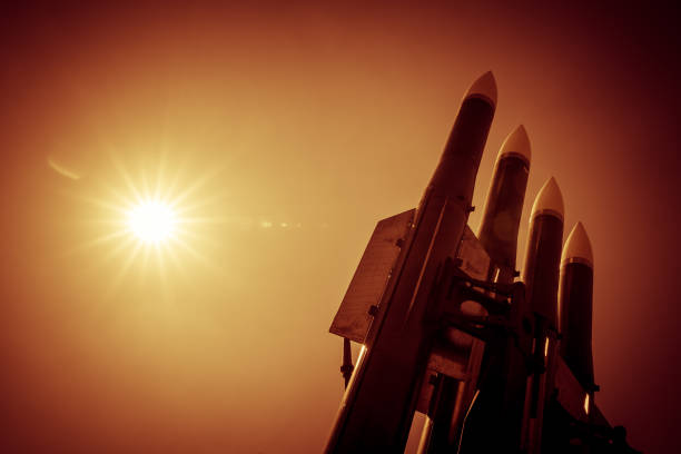 Four rockets of anti-aircraft missile system are directed upwards against a background of bright sun. Orange toned image Four rockets of anti-aircraft missile system are directed upwards against a background of bright sun. Orange toned image antiaircraft stock pictures, royalty-free photos & images