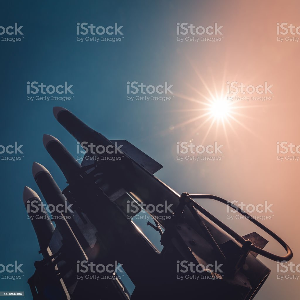 Four rockets of anti-aircraft missile system are directed upwards against the background of blue sky and sun at sunset stock photo
