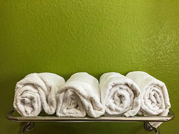four rolled white bath towels on shelf with green wall - sauna textilien stock-fotos und bilder