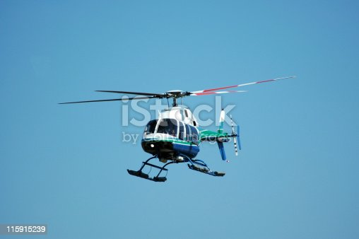 Four rotor, seven passenger helicopter against a clear sky. This helicopter is also used as an air ambulance. Bell 407.