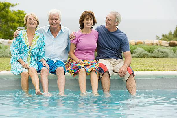 four senior adult friends dipping feet in a pool - old man feet stock photos and pictures