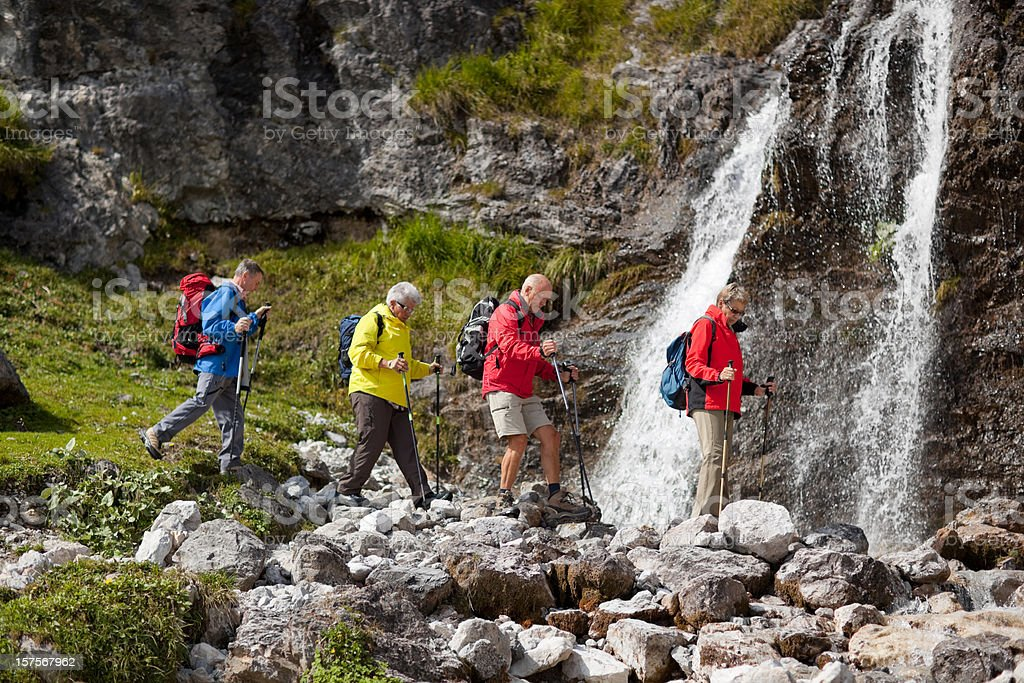 four senior hikers crossing river royalty-free stock photo