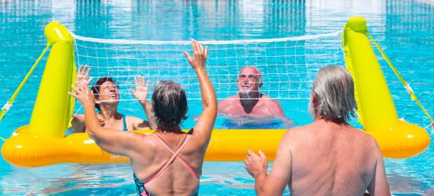 vier senioren im sport in das beckenwasser. sommer und helle sonne. schwimmendes volleyballnetz. blaues und transparentes wasser - senior bilder wasser stock-fotos und bilder