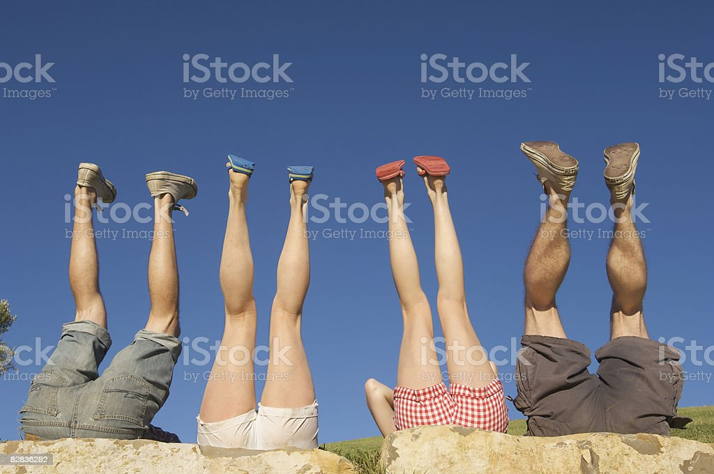 four sets of legs in the air against blue sky royaltyfri bildbanksbilder