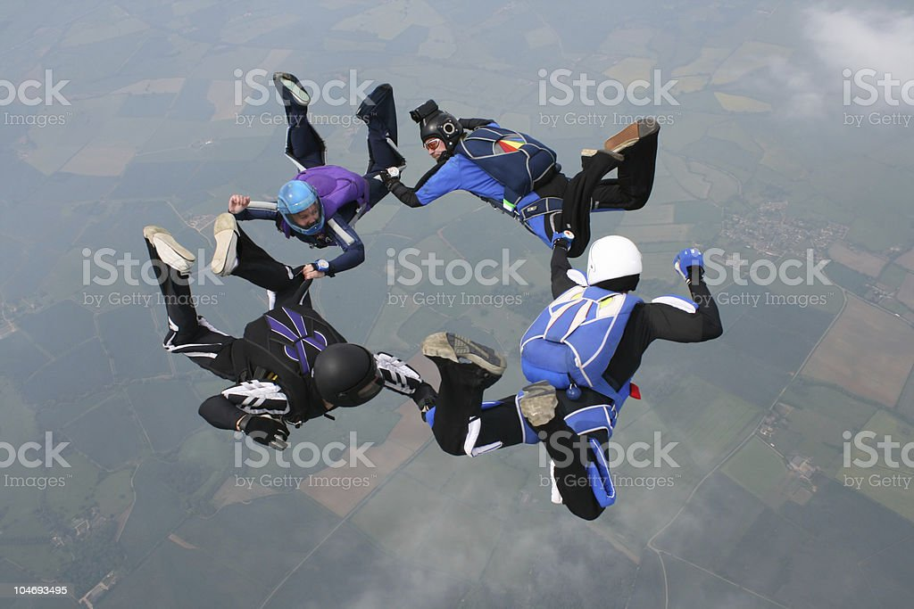 Four skydivers form a circle royalty-free stock photo