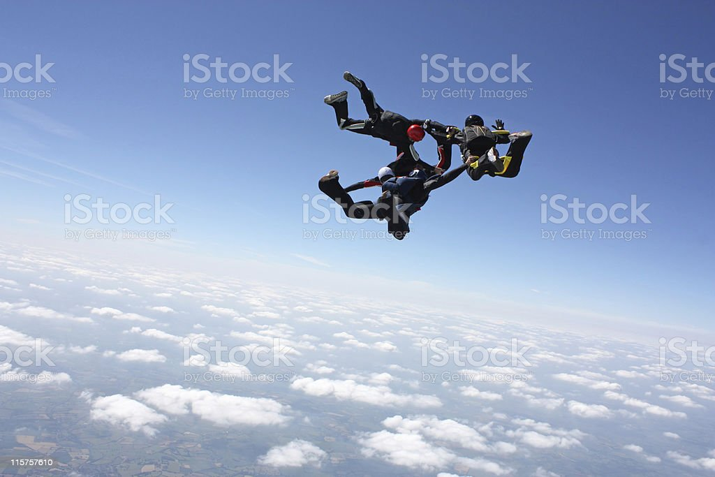 Four skydivers in formation during a free fall skydive stock photo