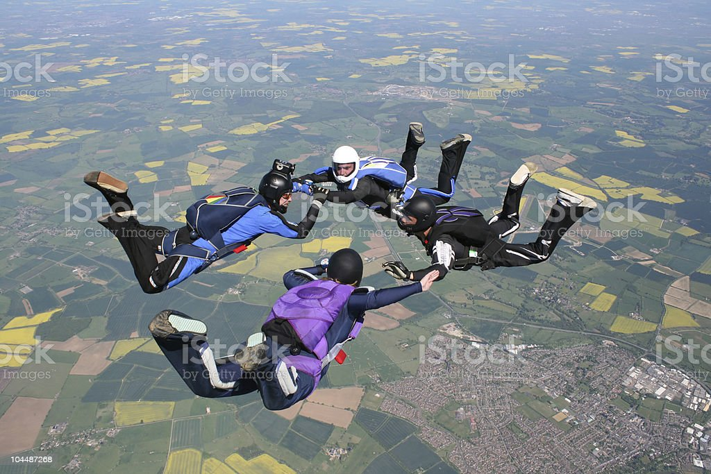 Four skydivers in freefall holding hands royalty-free stock photo