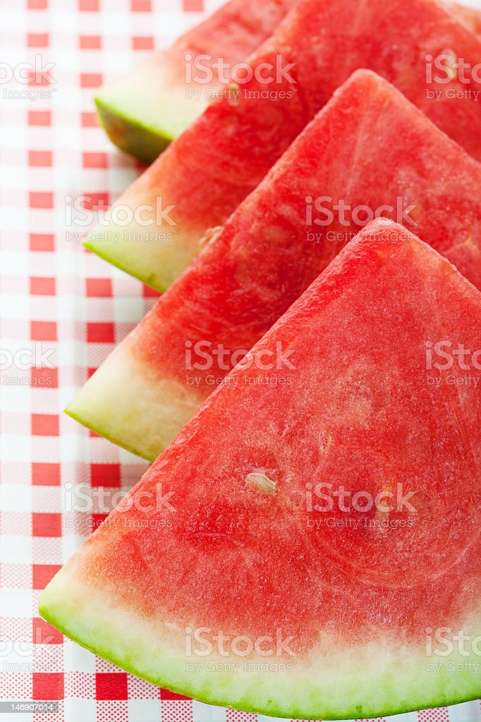 Four slices of watermelon and a squared pattern cloth royalty-free stock photo
