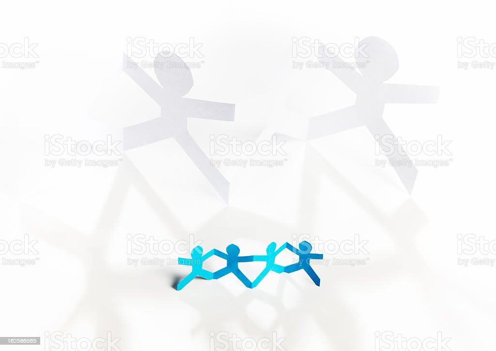 Four small blue paper-chain people overshadowed by two large ones stock photo