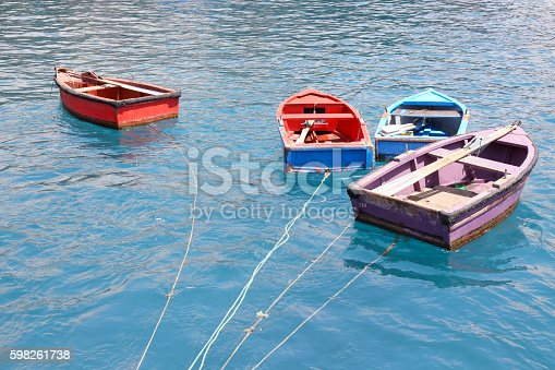 Four small boats moored in the port of Camera de Lobos in Madeira Island