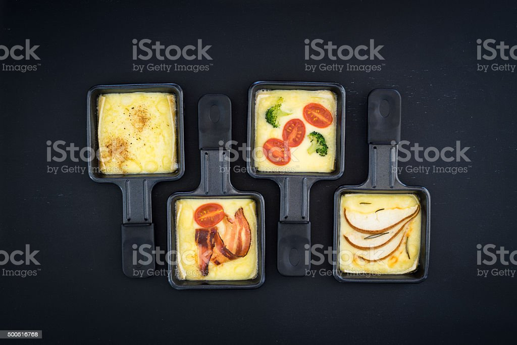 Four small raclette pans with cheese and different ingredients stock photo