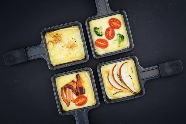 quatre petits raclette de fromage et poêles avec des produits différents - raclette photos et images de collection