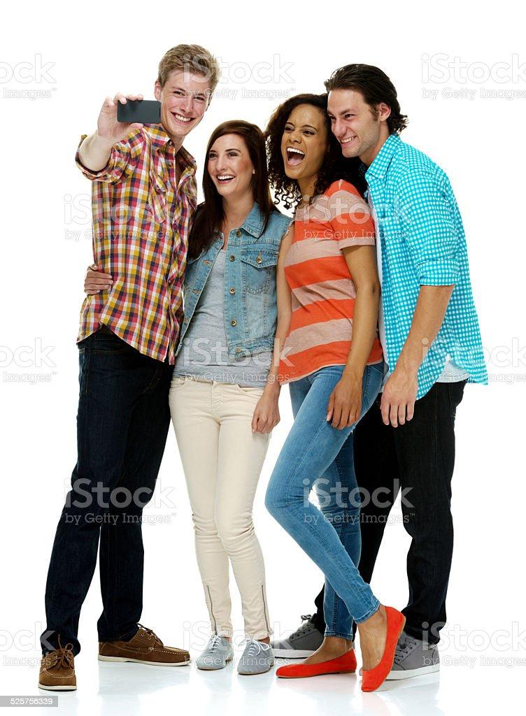 Quatro pessoas sorridente, fazendo uma selfie - foto de acervo